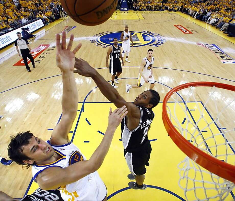 Andrew Bogut (12) gets a shot in past Kawhi Leonard (2) in the second half. The Golden State Warriors played the San Antonio Spurs in Game 4 of the Wester Conference Semifinals at Oracle Arena in Oakland, Calif., on Sunday, May 12, 2013. Photo: Carlos Avila Gonzalez, The Chronicle