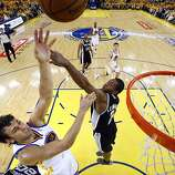 Andrew Bogut (12) gets a shot in past Kawhi Leonard (2) in the second half. The Golden State Warriors played the San Antonio Spurs in Game 4 of the Wester Conference Semifinals at Oracle Arena in Oakland, Calif., on Sunday, May 12, 2013.