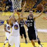 Andrew Bogut (12) defends against a shot by Manu Ginobli (20) in the second half. The Golden State Warriors played the San Antonio Spurs in Game 4 of the Wester Conference Semifinals at Oracle Arena in Oakland, Calif., on Sunday, May 12, 2013.