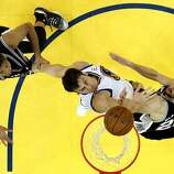 Andrew Bogut (12) defends against Tim Duncan (21) and Manu Ginobli (20) in the overtime period. The Golden State Warriors played the San Antonio Spurs in Game 4 of the Wester Conference Semifinals at Oracle Arena in Oakland, Calif., on Sunday, May 12, 2013.