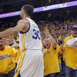 Stephen Curry (30) high fives fans in the second half. The Golden State Warriors played the San Antonio Spurs in Game 4 of the Wester Conference Semifinals at Oracle Arena in Oakland, Calif., on Sunday, May 12, 2013.