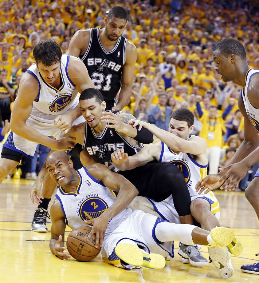 The Warriors' Jarrett Jack and Spurs' Danny Green grab for a loose ball between the Warriors' Andrew Bogut and Klay Thompson during second half action in Game 4 of the Western Conference semifinals Sunday, May 12, 2013 at Oracle Arena in Oakland. The Warriors won 97-87 in overtime.