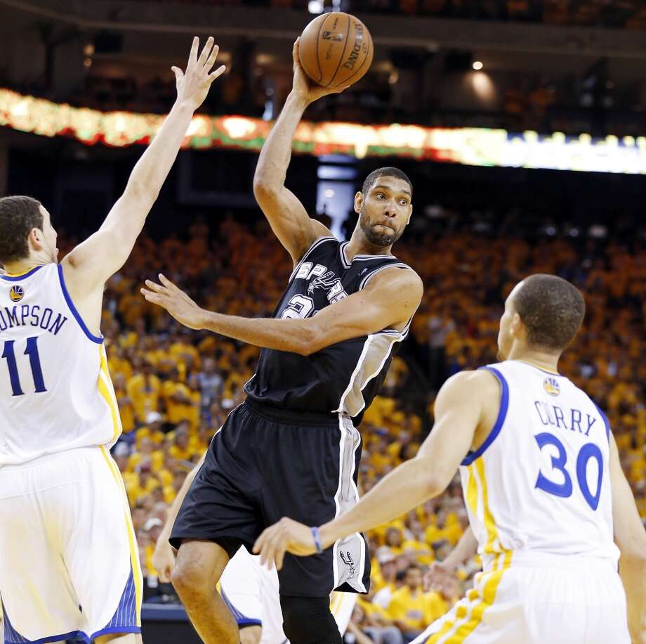 The Spurs' Tim Duncan passes between the Warriors' Klay Thompson and Stephen Curry during second half action in Game 4 of the Western Conference semifinals Sunday, May 12, 2013 at Oracle Arena in Oakland. The Warriors won 97-87 in overtime.