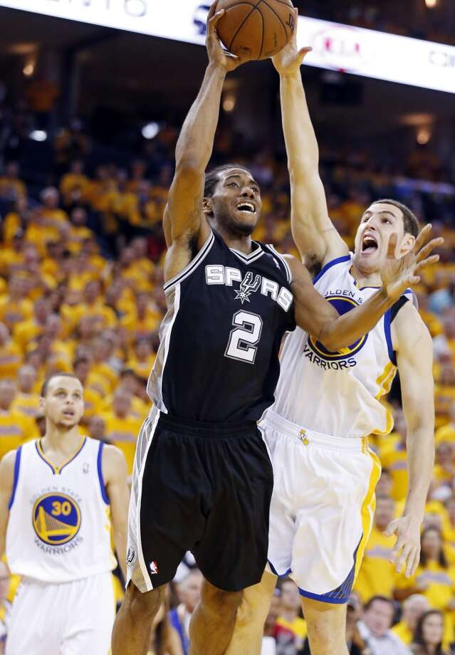 The Spurs' Kawhi Leonard shoots around the Warriors' Klay Thompson during second half action in Game 4 of the Western Conference semifinals Sunday, May 12, 2013 at Oracle Arena in Oakland. The Warriors won 97-87 in overtime.