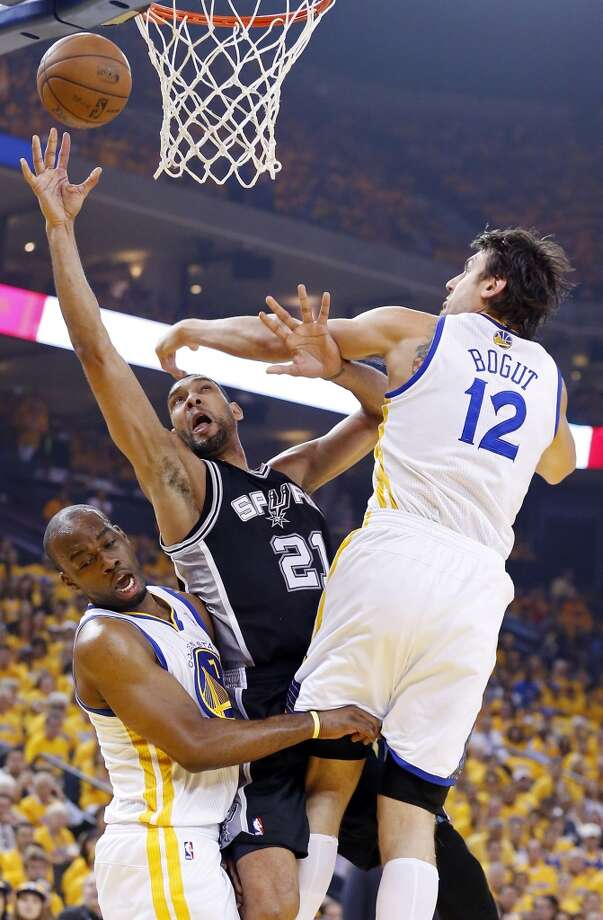 The Spurs' Tim Duncan shoots between the Warriors' Carl Landry and Andrew Bogut during first half action in Game 4 of the Western Conference semifinals Sunday, May 12, 2013 at Oracle Arena in Oakland.
