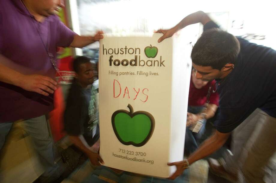 Volunteers help load donated food onto a loading dock at the grand opening ceremony for the new Houston Food Bank in September 2011.  The food bank took over the old Sysco distribution center. Photo: Brett Coomer, HC Staff / © 2011 Houston Chronicle