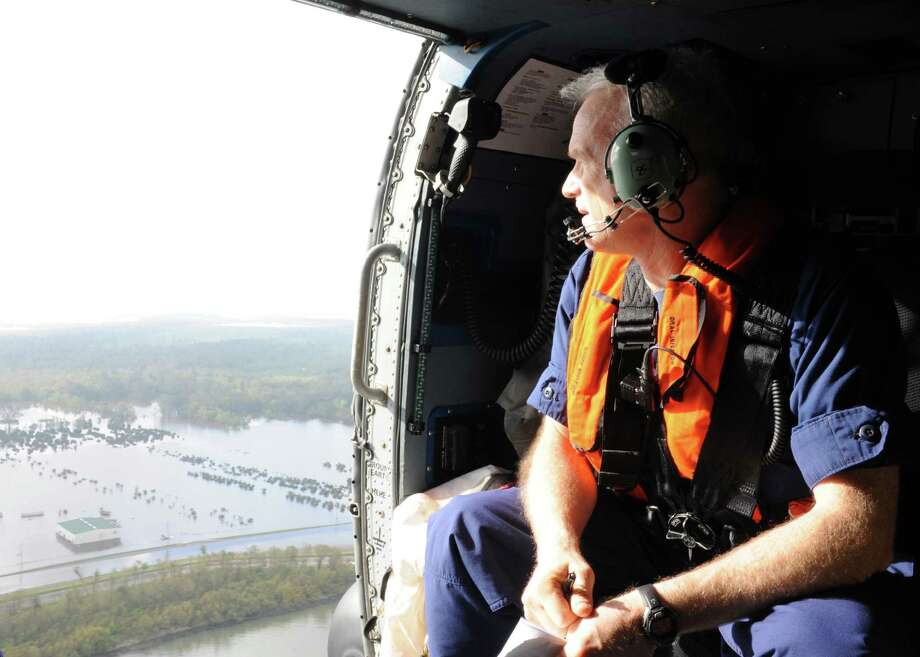 NEW ORLEANS ? Rear Adm. Roy Nash, Commander of the Eighth Coast Guard District, scans out the door of a helicopter on a survey flight of impacted areas, Sept. 1, 2012. Coast Guard officials surveyed the impacted areas for any potential navigation hazards, pollution or hazardous materials releases. U.S. Coast Guard photo by Petty Officer 1st Class Matthew Schofield.