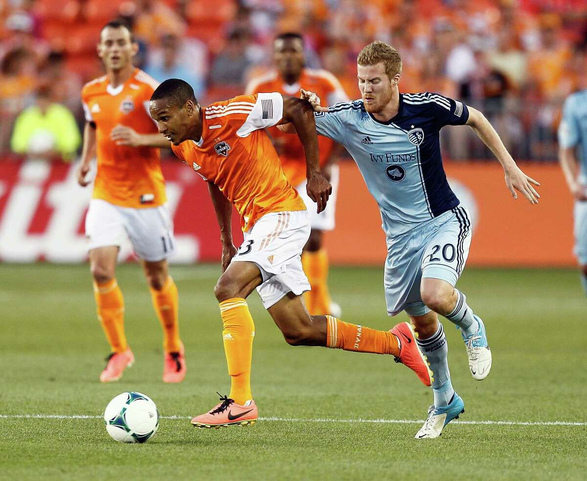Sporting KC 1, Dynamo 0 Houston Dynamo midfielder Ricardo Clark #13 is grabbed by Sporting KC midfielder Oriol Rosell #20 as he advances the ball during a MLS soccer match between the Houston Dynamo and the Sporting KC, Sunday May 12, 2013.(Bob Levey/For The Chronicle)