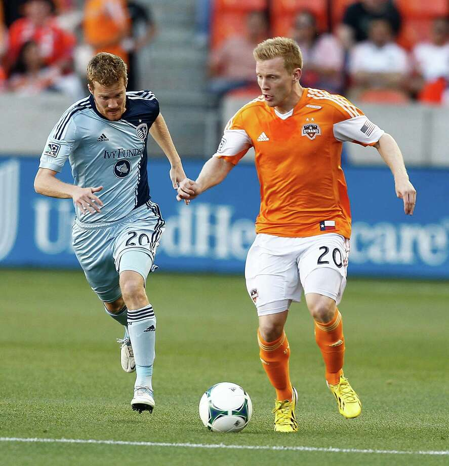 Houston Dynamo midfielder Andrew Driver #20 brings the ball up the field as he is pursued by Sporting KC midfielder Oriol Rosell #20 in the first half during a MLS soccer match between the Houston Dynamo and the Sporting KC, Sunday May 12, 2013.(Bob Levey/For The Chronicle) Photo: Bob Levey, Houston Chronicle / ©2013 Bob Levey