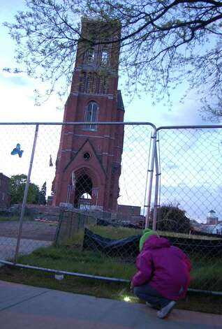 Olivia Miller, 6, brought a flashlight to a Sunday evening vigil on May 12, 2013, for the tower of St. Patrick's Church in Watervliet. The 123-year-old structure is scheduled to be torn down Monday morning. (Jimmy Vielkind/Times Union)