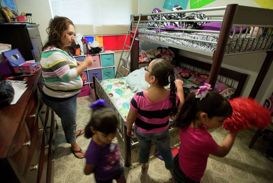 Darlene Dominguez searches for a missing pom-pom with her daughters, Khloe, 4, Ariella, 8, and Sarah, 6, at their home in San Antonio. Photo: Darren Abate, FRL