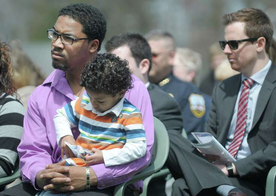 DC Dunkel holds his son, Damyis, 3, during a ceremony to honor victims of crime in Schenectady County at the rose garden in Central Park on Wednesday, April 24, 2013 in Schenectady, NY.  Dunkel is the uncle of Sha'hiim Nelligan, the 8-year-old boy who was recently beaten to death by his grandmother.    (Paul Buckowski / Times Union archvie) Photo: Paul Buckowski / 10022106A