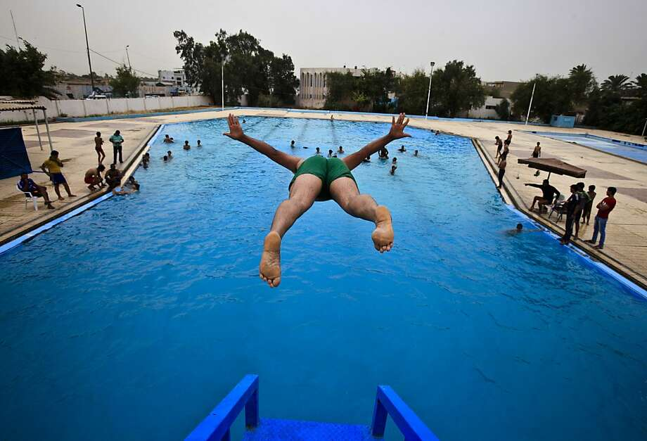An Iraqi man dives into a public swimming pool in Baghdad, Iraq, Sunday, May 12, 2013. (AP Photo/Karim Kadim) Photo: Karim Kadim, Associated Press