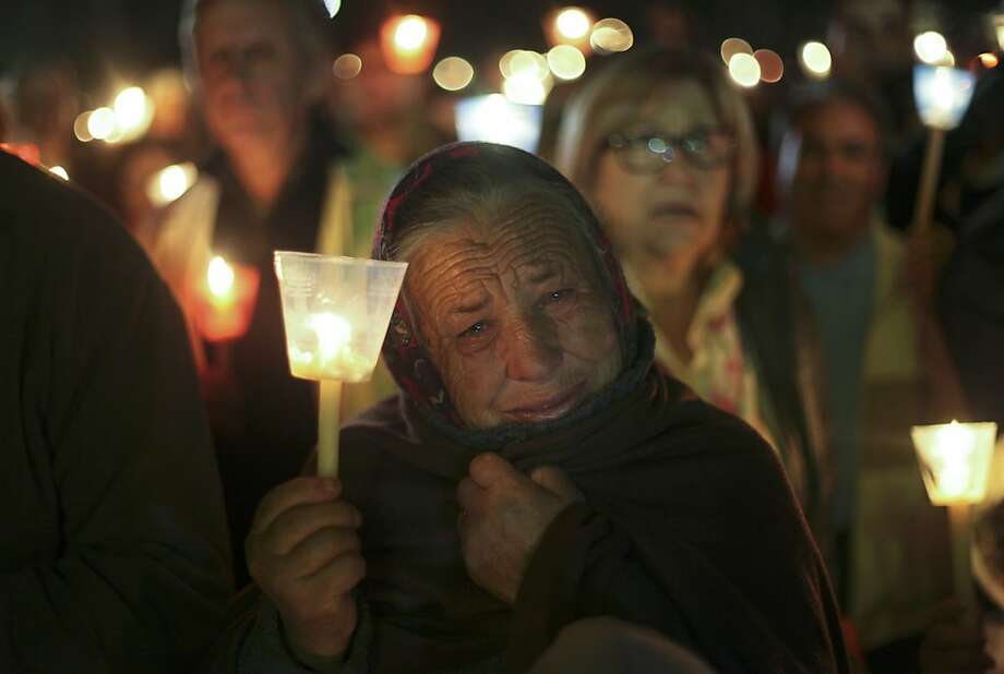 An elderly woman cries during a candle light vigil at the Fatima Sanctuary in Fatima, center Portugal, Sunday, May 12, 2013. Every year on May 12 and 13, thousands of Catholic faithfuls pilgrimage to Fatima's Sanctuary where it is believed the Virgin Mary was witnessed by three shepherd children, Lucia, Jacinta and Francisco on May 13, 1917. (AP Photo/Francisco Seco) Photo: Francisco Seco, Associated Press