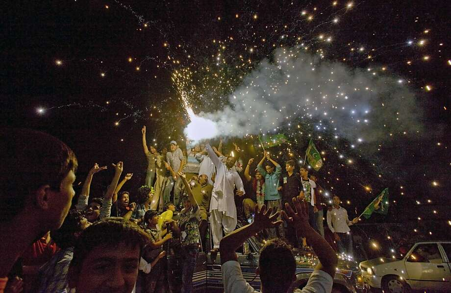 Supporters of Pakistan Muslim League-N party release firework to celebrate their party victory in the parliamentary election at outside the party's headquarter in Lahore, Pakistan, Sunday, May 12, 2013. Former Pakistani Prime Minister Nawaz Sharif looked set Sunday to return to power for a third term, with an overwhelming election tally that just weeks ago seemed out of reach for a man who had been ousted by a coup and was exiled abroad before clawing his way back as an opposition leader. (AP Photo/Anjum Naveed) Photo: Anjum Naveed, Associated Press