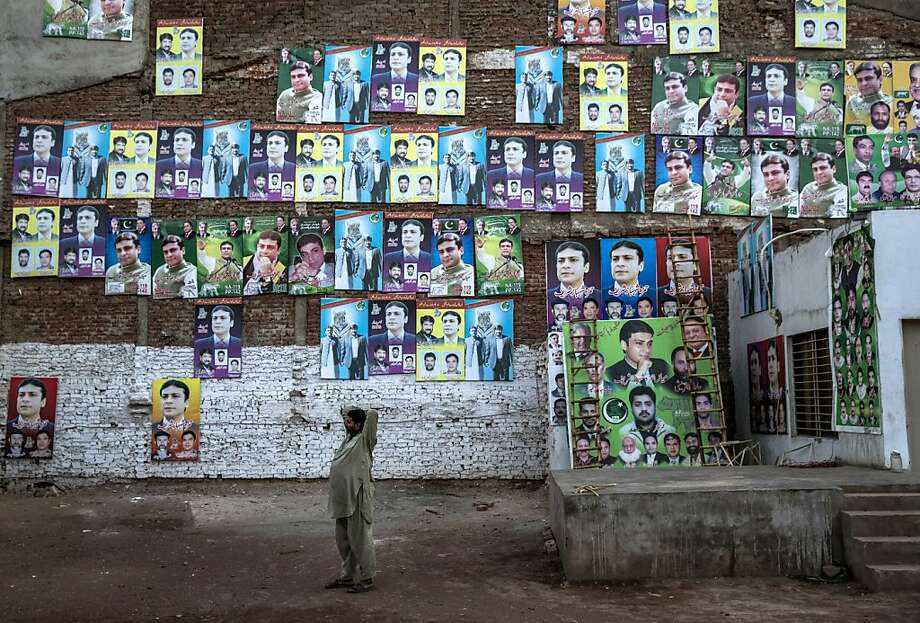 LAHORE, PAKISTAN - MAY 12: A man talks on his phone as he stands in front of a wall pastered wth PML-N party election campaign posters the day after election day on May 12, 2013 in the Old City of Lahore, Pakistan. The electoral committee recorded a high voter turn out as millions of Pakistanis cast their votes in yesterdays parliamentary elections. It is the first time in the country's history that an elected government will hand over power to another elected government. Initial results show the PML-N party has recorded the highest number of seats won and party leader.Nawaz Sharif has claimed victory ahead of the last official results.  (Photo by Daniel Berehulak/Getty Images) *** BESTPIX *** Photo: Daniel Berehulak, Getty Images