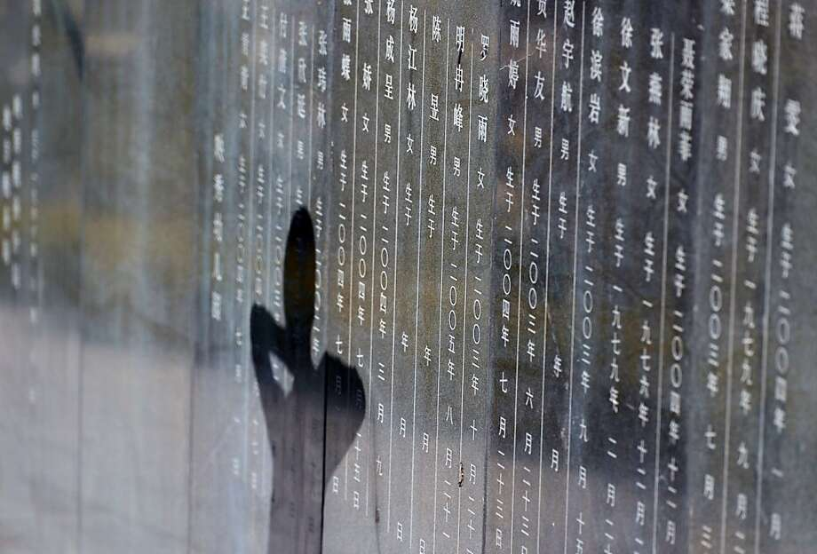 TOPSHOTS A shadow is seen on the monument of the 5/12 Sichuan earthquake as residents gather to give their condolence on the 5th anniversary of the disaster on May 12, 2013, in Yingxiu township of Wenchuan county, southwest China's Sichuan province.  Five years after thousands of Chinese children died as their schools collapsed in an earthquake, new babies have given devastated families hope even as questions over poor building work and corruption remain. CHINA OUT   AFP PHOTOSTR/AFP/Getty Images Photo: Str, AFP/Getty Images