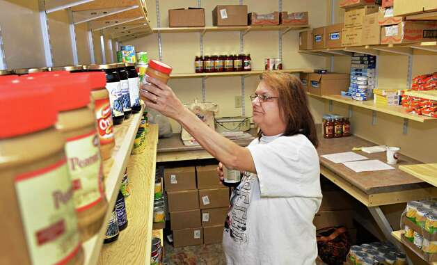 Congregant Suzanne Fox of Johnstown stocks shelves at the food pantry in the newly rebuilt Mayfield Presbyterian Church in Mayfield, NY Tuesday May 7, 2013.  (John Carl D'Annibale / Times Union Photo: John Carl D'Annibale / 00022307A