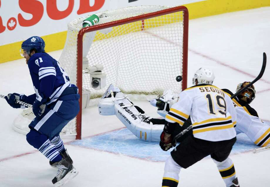 Toronto Maple Leafs forward Phil Kessel, left, scores past Boston Bruins goalie Tuuka Rask, right, as Bruins forward Tyler Seguin back centre, looks on during third period NHL hockey playoff action in Toronto on Sunday, May 12, 2013. Photo: The Canadian Press, Nathan Denette