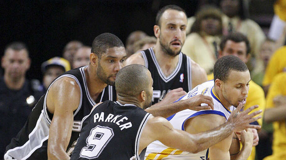 The Spurs' Tim Duncan (from left), Tony Parker and Manu Ginobili trap the Warriors' Stephen Curry during overtime of the Warriors' victory on Sunday in Oakland, Calif. Edward A. Ornelas / San Antonio Express-News