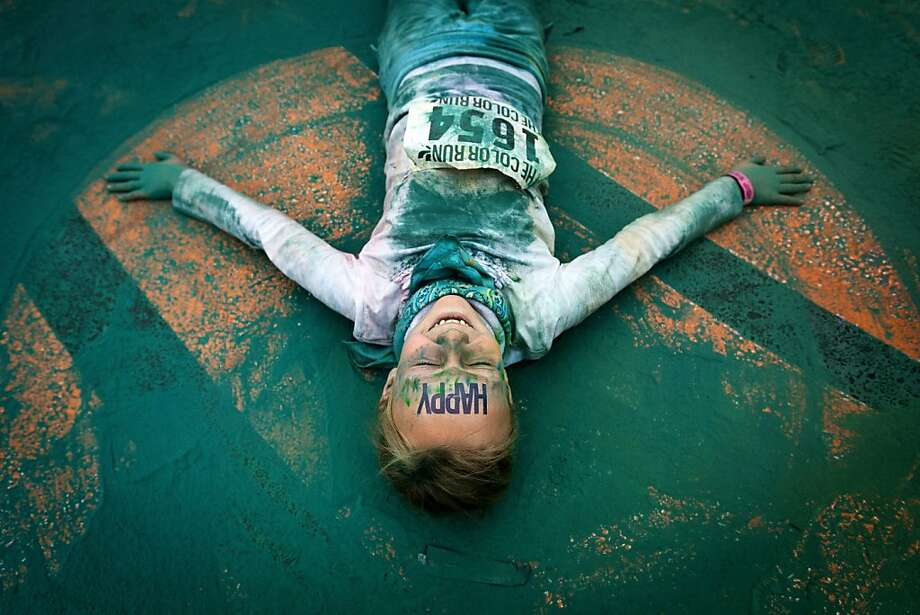 A young girl makes a chalk angel in the powdery madness covering the ground following the Color Run 5k Sunday, May 12, 2013, in Seattle, Wash. The sold out event - also known as the Happiest 5k on the Planet - is a unique paint race celebrating healthiness, happiness and individuality. (AP Photo/seattlepi.com, Jordan Stead) Photo: Jordan Stead, Associated Press