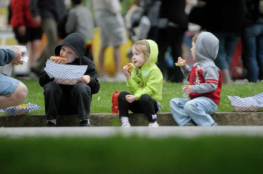 From left to right, Francesco Sirtori, 7, and his twin siblings Theresa and Tyler, 3, from Latham enjoy hotdogs during the Albany Tulip Festival at Washington Park on Sunday, May 12, 2013 in Albany, NY.   (Paul Buckowski / Times Union) Photo: Paul Buckowski