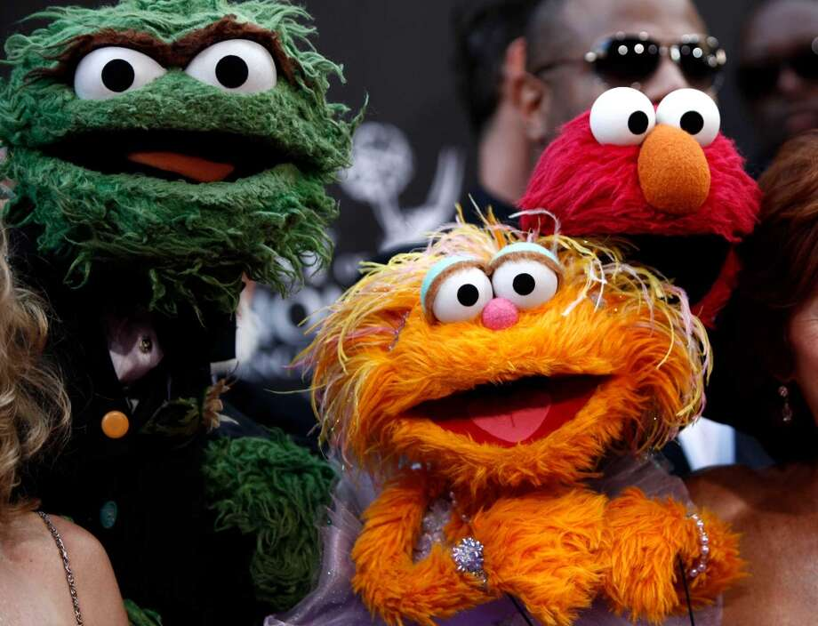 Zoe, center, was introduced in 1993, to help combat the overwhelming guy-ness of the Muppet crew. She looked a little like Elmo, except that she was orange, had a button nose, and wore barrettes and jewelry.