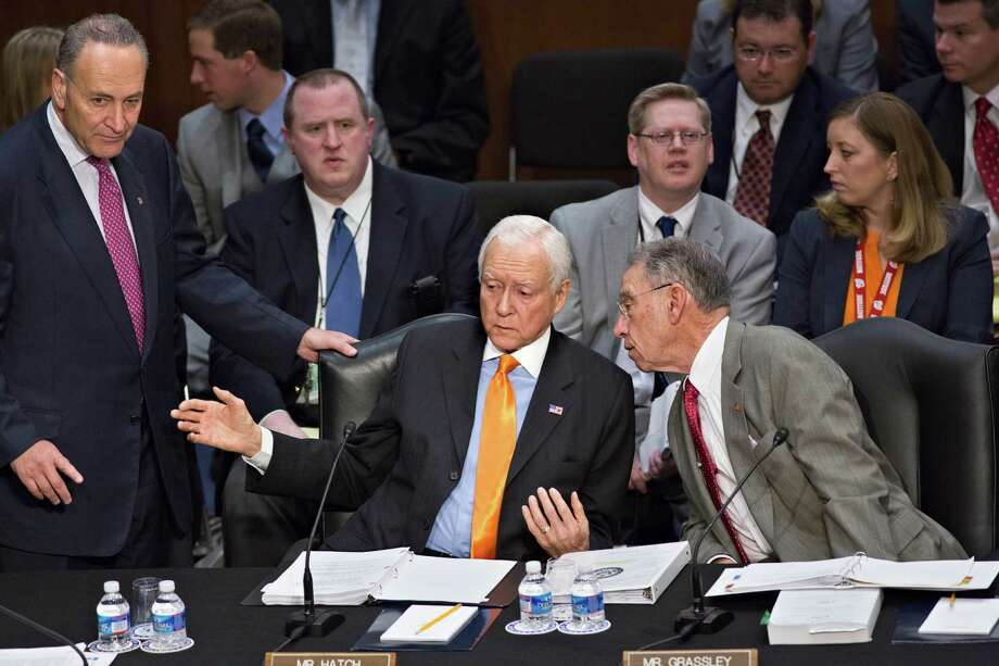 From left, Sen. Chuck Schumer, D-N.Y., standing, Sen. Orrin G. Hatch, R-Utah, and Sen. Chuck Grassley, R-Iowa, confer as the Senate Judiciary Committee meets on immigration reform on Capitol Hill in Washington, Thursday, May 9, 2013. A bill to enact dramatic changes to the nation's immigration system and put some 11 million immigrants here illegally on a path to citizenship is facing its first congressional test as the Senate Judiciary Committee begins considering proposed changes to the 844-page legislation.  (AP Photo/J. Scott Applewhite) Photo: J. Scott Applewhite, Associated Press / AP