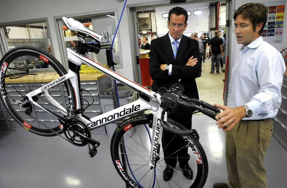 In this file photo taken on Aug. 14, 2012, Gov. Dannel P. Malloy, center, listens to Jeff McGuane describe the Slice RS Triathlon bike at the grand opening of the research and development facility for Cycling Sports Group in Bethel. McGuane is president of Cycling Sports Group that includes Cannondale, GT Bicycles, Schwinn and Mongoose brands. Photo: Michael Duffy / The News-Times