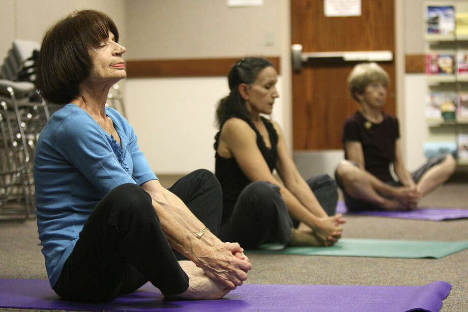 Several women relax during a yoga class offered by OASIS, a nonprofit that offers a variety of free or low-cost classes for seniors.  Though the economy is on the rebound, low-cost events and activities are increasingly popular. Photo: Express-News File Photo