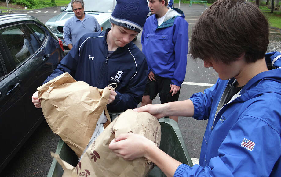 Staples High School students Daniel Brill and Connor Mitnick empty papers dropped off by town residents Saturday into a trash toter, ready for disposal at Westport's Shred Day program. Photo: Mike Lauterborn / Westport News contributed