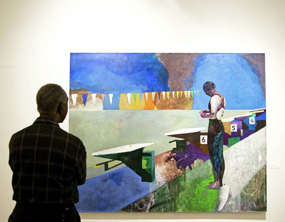 "A viewer looks at Sky Patterson's ""Swimmer with Starting Blocks & Flags"" at Blue Star. Photo: Courtesy Emily Messer"