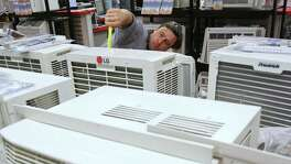 Jean Pierre Bernard measures an air conditioner while shopping at PC Richard & Son, Thursday, July 27, 2006, in New York. Orders for U.S.-made durable goods rose more than forecast in June, pointing to momentum in manufacturing that's likely to buttress the economy even as the housing market sputters. Photographer: Stephen Hilger/Bloomberg News.