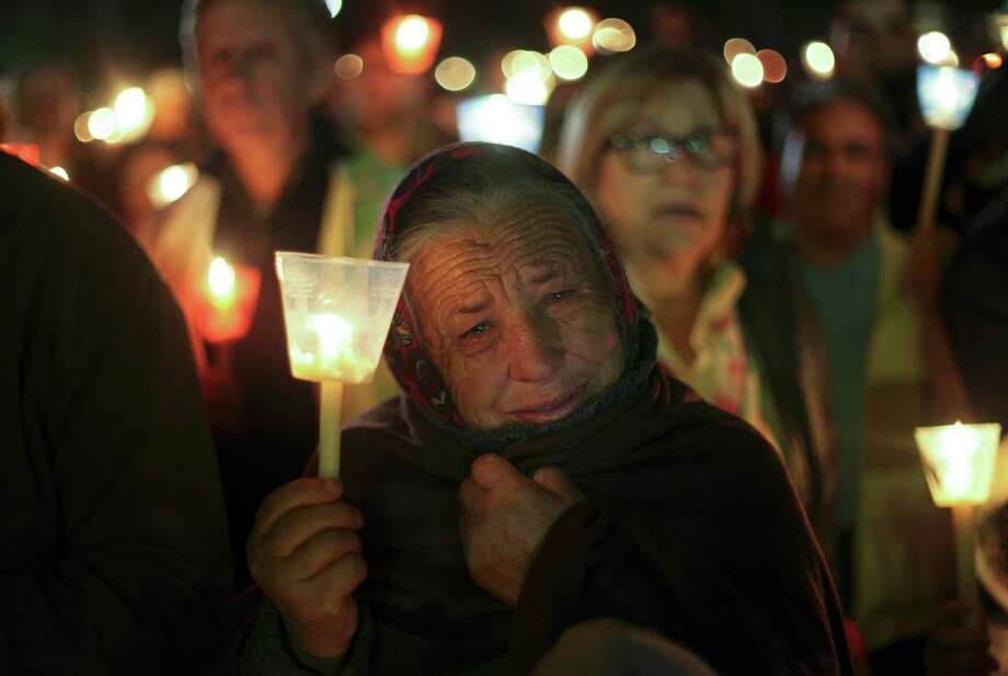 An elderly woman cries during a candle light vigil at the Fatima Sanctuary in Fatima, center Portugal, Sunday, May 12, 2013. Every year on May 12 and 13, thousands of Catholic faithfuls pilgrimage to Fatima's Sanctuary where it is believed the Virgin Mary was witnessed by three shepherd children, Lucia, Jacinta and Francisco on May 13, 1917. Photo: Francisco Seco, Associated Press / AP