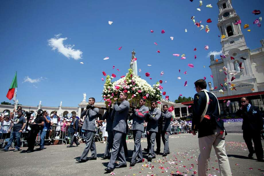 The statue of the Our Lady of Fatima is carried during a mass ceremony at the Fatima catholic shrine in Fatima, central Portugal, on May 13, 2013. Thousands of pilgrims converged on Fatima Santuary to celebrate the anniversary of the Fatima miracle when three shepherd children claimed to having seen the Virgin Mary in May 1917. Photo: PEDRO NUNES, AFP/Getty Images / AFP