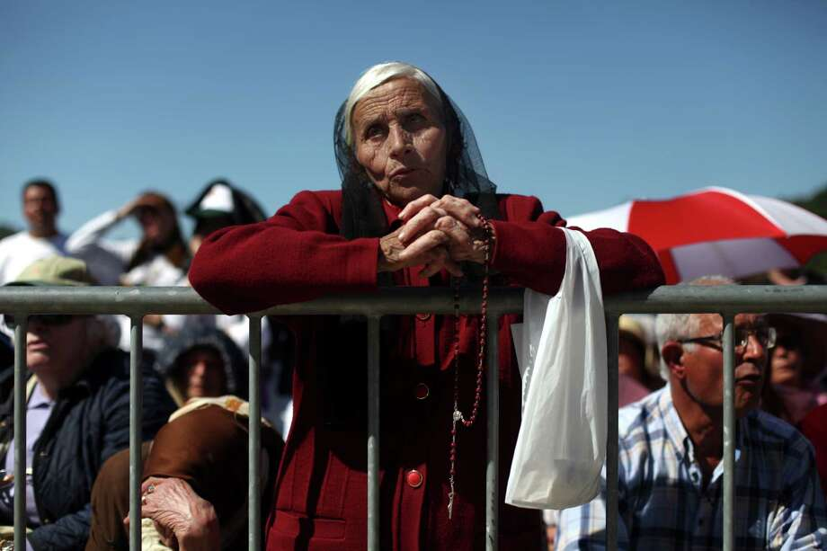An elderly woman prays during a mass at the Our Lady of Fatima shrine in Fatima, central Portugal, Monday, May 13, 2013. Every year on May 12 and 13, thousands of Catholic faithful pilgrimage to Fatima's Sanctuary where it is believed the Virgin Mary was witnessed by three shepherd children, Lucia, Jacinta and Francisco, on May 13, 1917. Photo: Francisco Seco, Associated Press / AP