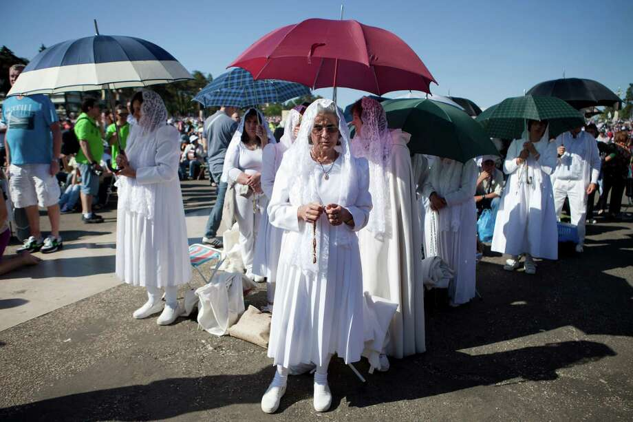 Pilgrims attend a mass ceremony at the Fatima catholic shrine in Fatima, central Portugal, on May 13, 2013. Thousands of pilgrims converged on Fatima Santuary to celebrate the anniversary of the Fatima miracle when three shepherd children claimed to having seen the Virgin Mary in May 1917. Photo: PEDRO NUNES, AFP/Getty Images / AFP