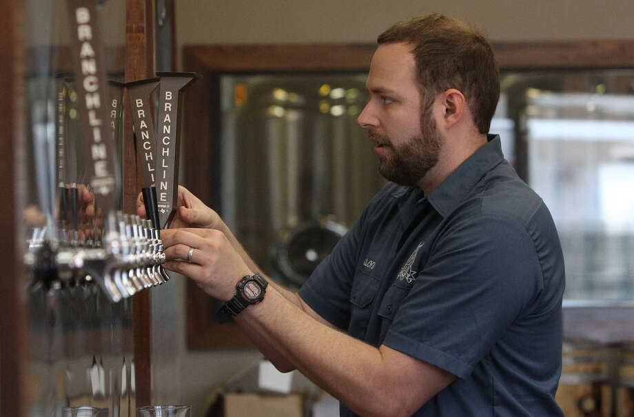 Jason Ard, owner of Branchline Brewing Co., works on newly installed equipment at his business. Photo: Express-News File Photo
