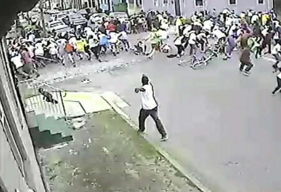 "This video grab image courtesy of the New Orleans Police Department shows a surveillance video of one of the suspects in the Motherâ??s Day shooting that left 19 wounded on May 12, 2013 in New Orleans, Louisiana. He is in a white T-shirt and dark pants, and is straddling the curb and the street.  Nineteen people were hurt in a shooting at a Mother's Day parade in New Orleans Sunday, police said, as the mayor called for an end to ""relentless"" violence on the streets of the southeastern US city.Those wounded by the eruption of gunfire in the early afternoon attack included 17 adults and two 10-year-olds, the local police department said in a statement.""Many of the victims were grazed (some by bullets that ricocheted),"" it said. ""At this point, there are no fatalities, and most of the wounds are not life-threatening."" AFP PHOTO / NEW ORLEANS POLICE DEPARTMENT == RESTRICTED TO EDITORIAL USE / MANDATORY CREDIT: ""AFP PHOTO / NEW ORLEANS POLICE DEPARTMENT / NO MARKETING / NO ADVERTISING CAMPAIGNS / DISTRIBUTED AS A SERVICE TO CLIENTS ==HO/AFP/Getty Images Photo: Ho, AFP/Getty Images"