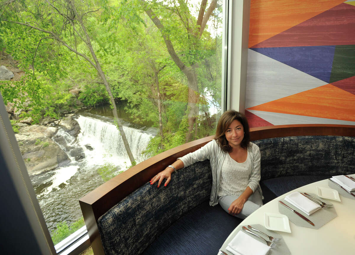 Mia Schipani, the spokesperson for RMS Construction and Hoel Zero Degrees in Norwalk, sits in front of a window overlooking the Norwalk River in Mediterraneo, the restaurant located within Hotel Zero Degrees, in Norwalk on Monday, May 13, 2013.