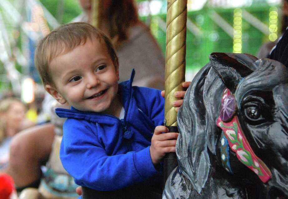 Sixteen-month-old Cooper Schulman rides the carousel at St. Mark's May Fair in 2013. Photo: Jeanna Petersen Shepard / New Canaan News Freelance