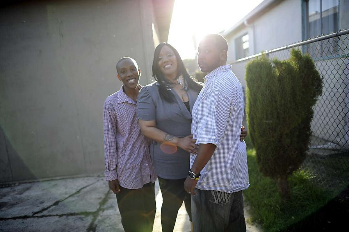 Wakeelah and Andre Davis pose for a portrait with their son Dre'onn, 13, in the backyard of their home in Richmond, CA Tuesday May 7th, 2013. The Davis family recently bought their home with the help of the nonprofit Self Help, which buys and fixes up foreclosures for sale to low-income owners.