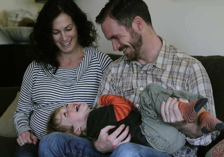 Nyree Bekarian (left) and Hunter Mack play with their son Emmett in their rental duplex in Oakland. The family has been frustrated shopping for a home by multiple bids and cash buyers. Photo: Paul Chinn, The Chronicle
