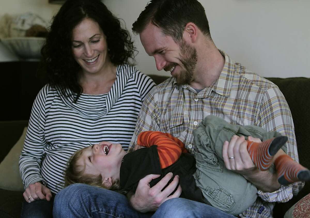 Nyree Bekarian (left) and Hunter Mack play with their son Emmett, 2, in the living room of their rental duplex in Oakland, Calif. on Friday, May 10, 2013. The family has been attempting to buy their own home for several months but are frustrated by multiple bids and buyers paying cash.