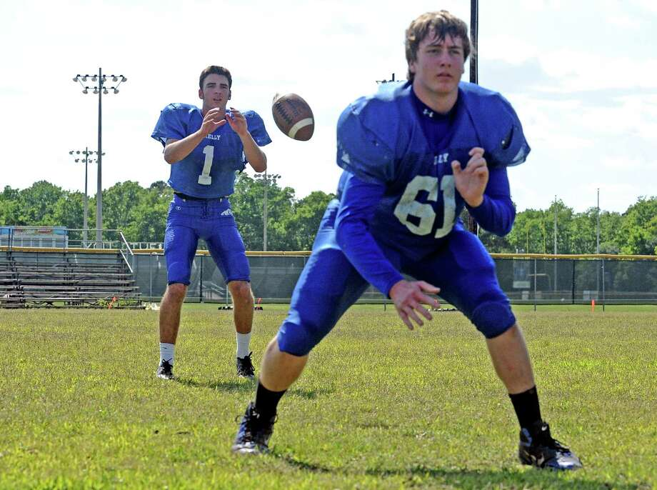 Matt Avanzato, right, hikes the ball to Conner Moore, center, during the Monsignor Kelly Catholic High School spring football practice on Tuesday, May 7, 2013. Photo taken: Randy Edwards/The Enterprise Photo: Randy Edwards