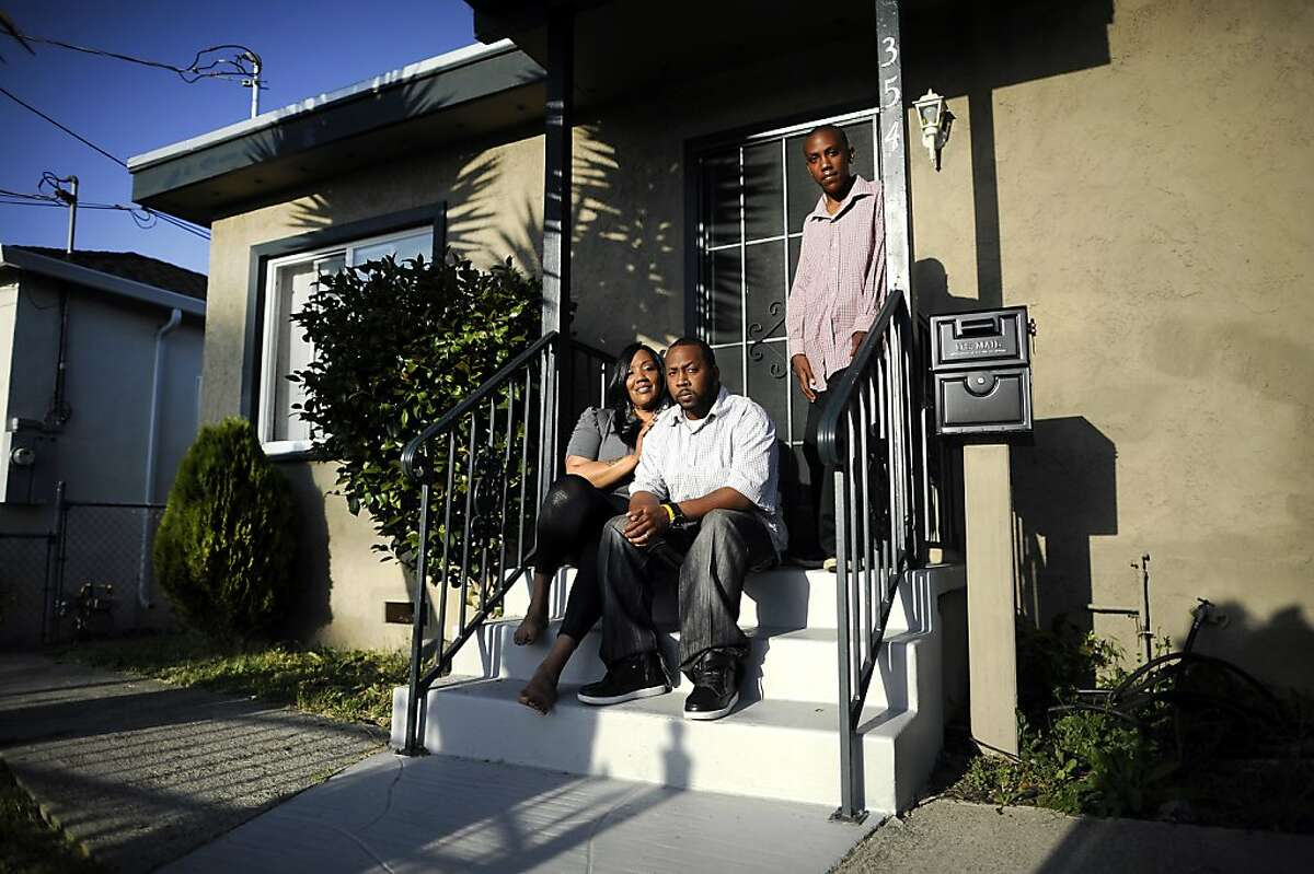 Wakeelah and Andre Davis pose for a portrait with their son Dre'onn, 13, on the front porch of their home in Richmond, CA Tuesday May 7th, 2013. The Davis family recently bought their home with the help of the nonprofit Self Help, which buys and fixes up foreclosures for sale to low-income owners.