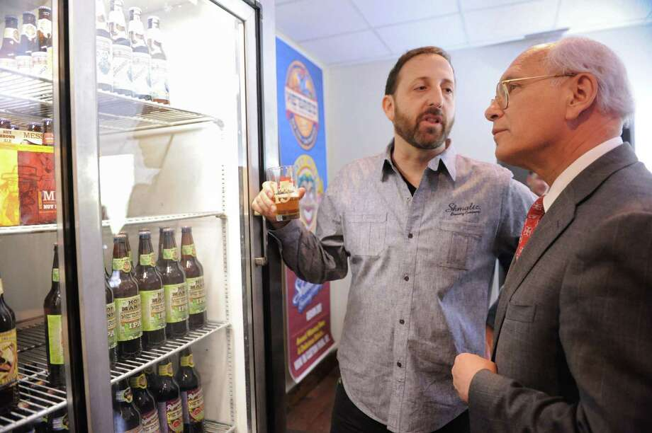 Owner Jeremy Cowan talks to Congressman Paul Tonko about the kinds of beer in a case during a ribbon cutting ceremony for Shmaltz Brewing Company's new 50- barrel brewery on Monday, May 13, 2013 in Clifton Park, N.Y. (Lori Van Buren / Times Union) Photo: Lori Van Buren / 00022392A