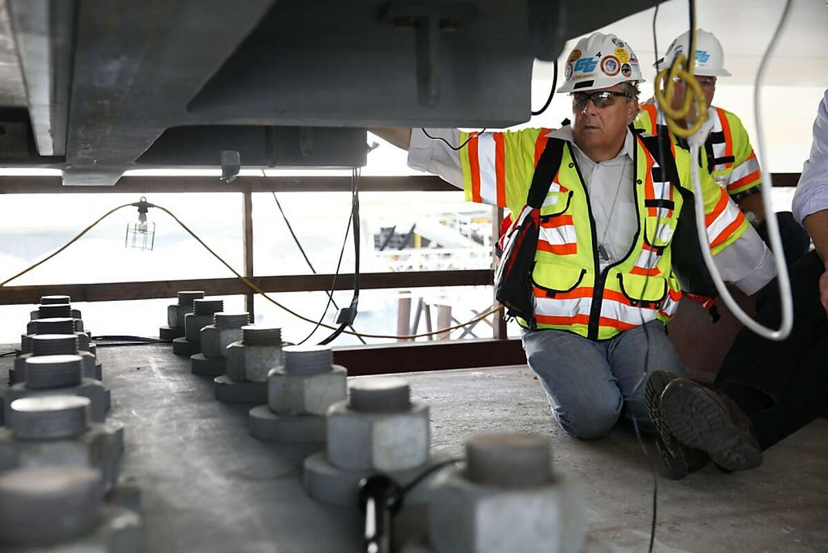Tony Anziano, Caltrans' toll bridge program manager, sits next to a shear key with no broken anchor rods under the new Bay Bridge on Friday, May 3, 2013.