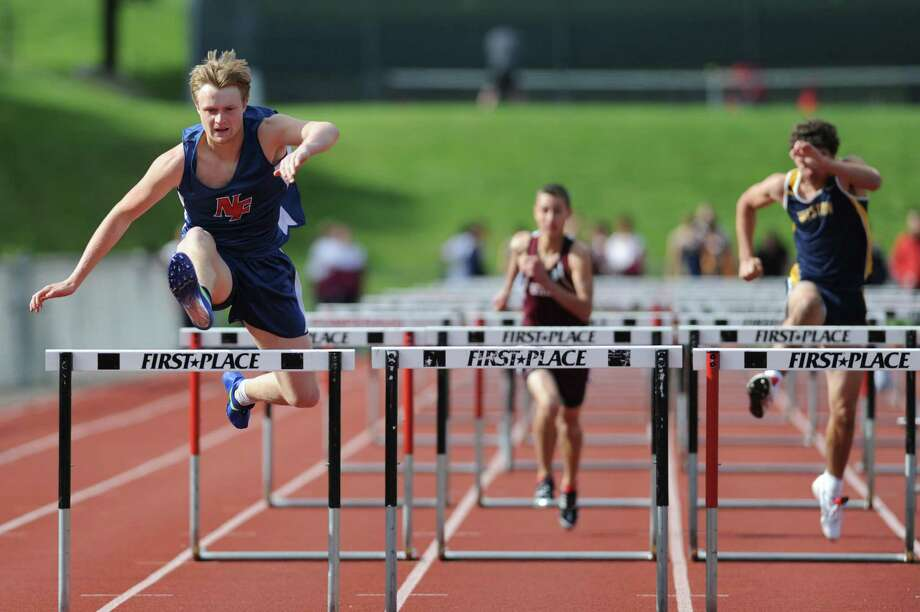 New Fairfield's Carter Johnson, left, competes in the 100 meter hurdles at the track and field meet between Pomperaug, New Fairfield, Bethel and Weston at Pomperaug High School in Southbury, Conn. on Monday, May 13, 2013.  Carter got first place overall in the event and New Fairfield won the meet, completing its second consecutive undefeated regular season. Photo: Tyler Sizemore / The News-Times