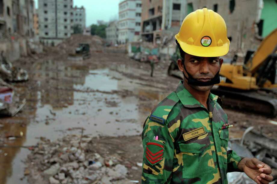 A Bangladeshi soldier stands at the site where a Bangladesh garment-factory building collapsed on April 24 in Savar, near Dhaka, Bangladesh, Monday, May 13, 2013.Nearly three weeks after the building collapsed, the search for the dead ended Monday at the site of the worst disaster in the history of the global garment industry. (AP Photo/A.M. Ahad) Photo: A.M. Ahad